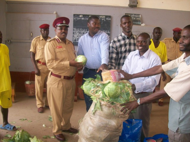 John Mugabi (in blue next to guard) bringing food supplies to a prison