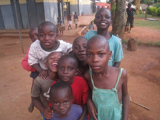 Isaac is the boy in the green overalls.  He is from Gulu, an area in Northern Uganda where Invisible Children is - they have several child soliders in this area.  Isaac's mom was a solider and recently died from AIDS.